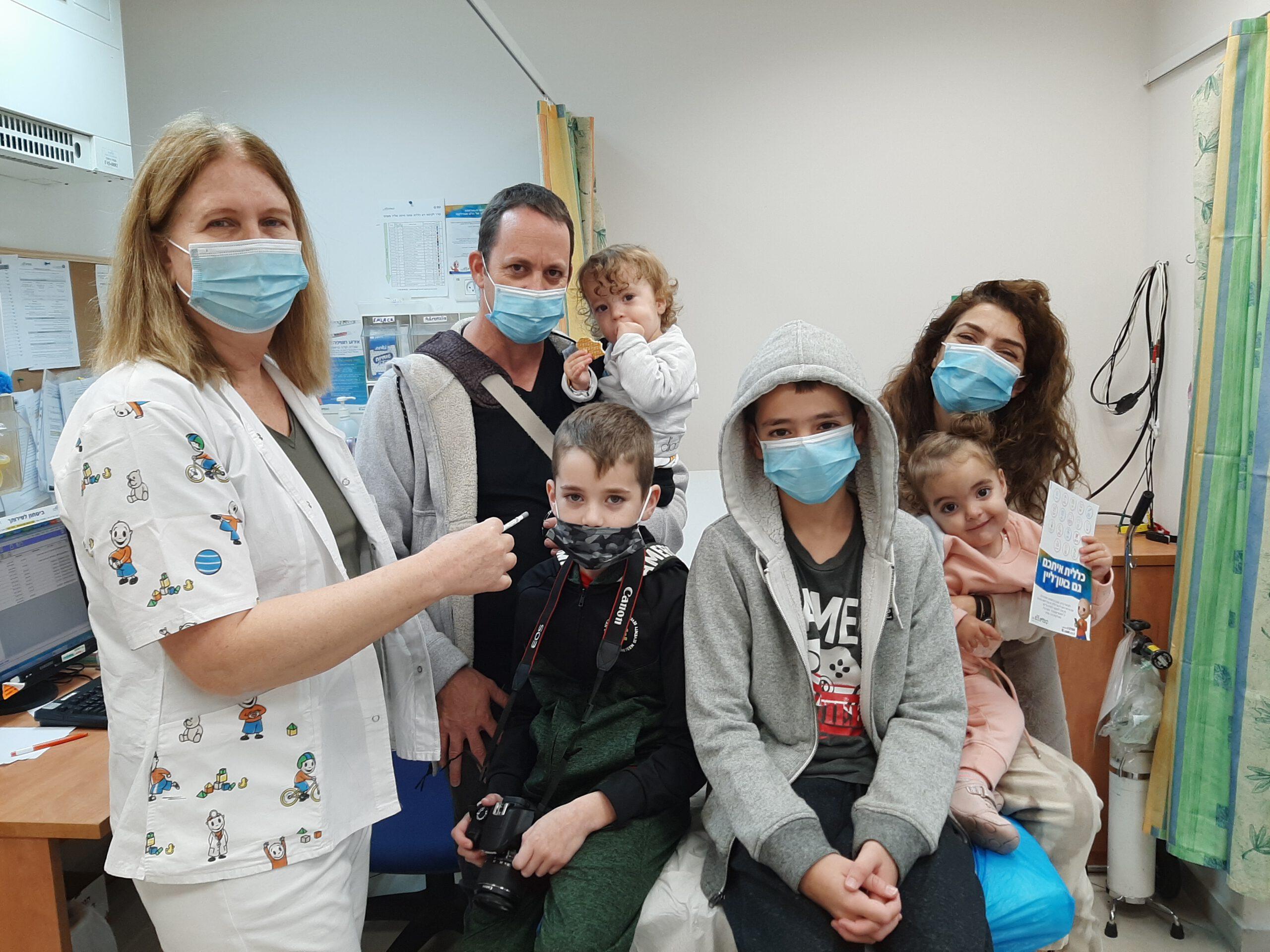 משפחה מתחסנת נגד השפעת במרכז הילד של כללית במחוז