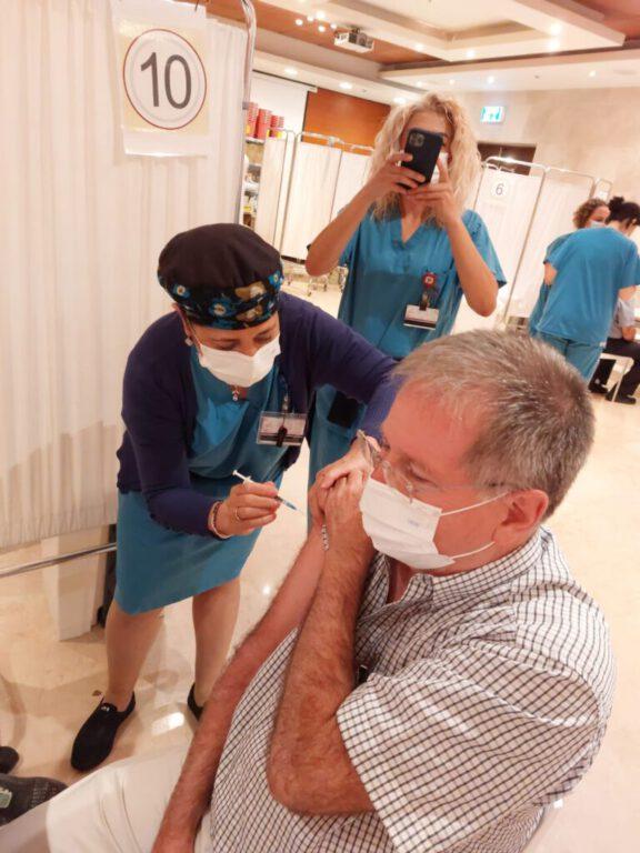 """בתמונה: ד""""ר מיקי הלברטל מקבל את זריקת החיסון השלישית מידה של האחות מיכל קרנצלר קרדיט: דוברות הקריה הרפואית רמב""""ם"""
